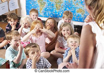 nauczyciel, montessori/pre-school, klasa, słuchający, dywan