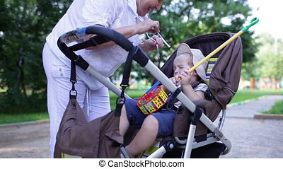Naughty boy in the buggy with granny. Middle shot.