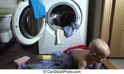 Naughty child boy making mess with laundry in bathroom....
