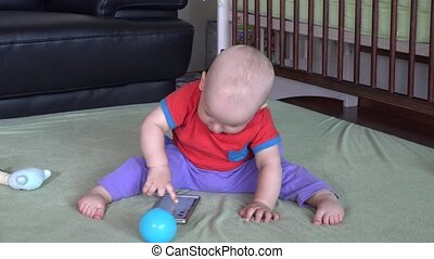 Naughty child boy play with smartphone at home. Static closeup shot.