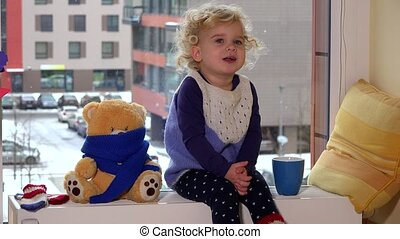 Naughty child boy with tea cup and best friend teddy bear...