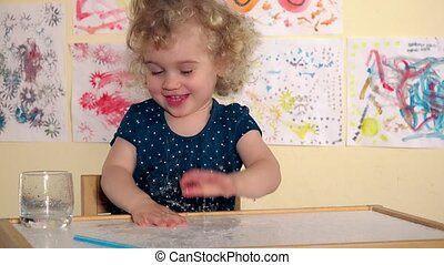 Naughty child girl spatter water on table. Excited wet girl....