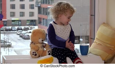 Naughty child girl with tea cup and friend teddy bear sit near window