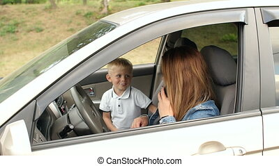 Naughty child interferes with mom in a car, he closes her eyes with his hands.