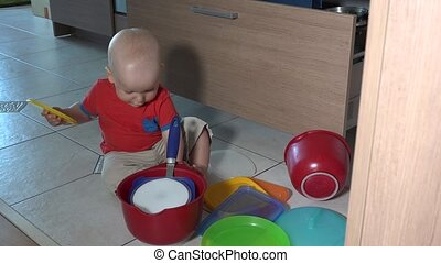 Naughty child playing with bowls on kitchen floor. Static...