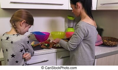 Naughty daughter near mother in the kitchen