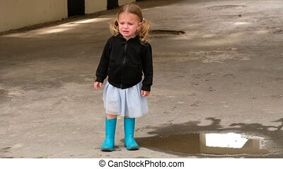 Full body capricious girl in boots crying and stamping foot while standing near puddle of water on street