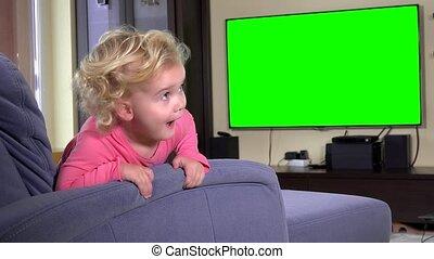 Naughty girl watching tv sitting on sofa. Green chroma key screen