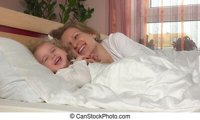 Naughty laughing girl lie down near her mother in bed....
