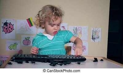 Naughty little child destroy computer keyboard on table....