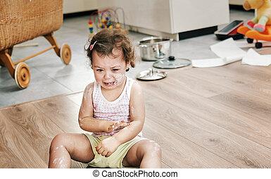 Naughty little girl sitting on the floor
