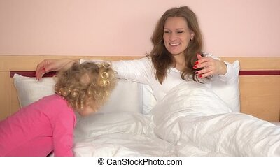 Naughty little girl came in bed and hug her mother. Lovely...