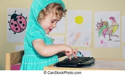 Naughty little girl child typing keyboard and talking with herself