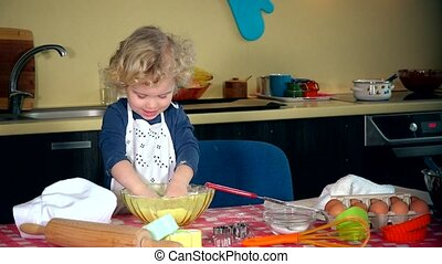 Naughty little girl clap hands with flour covered hands. mini chef in kitchen