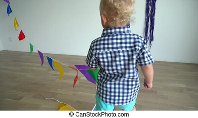 Naughty toddler boy playing with colorful flags. Gimbal...
