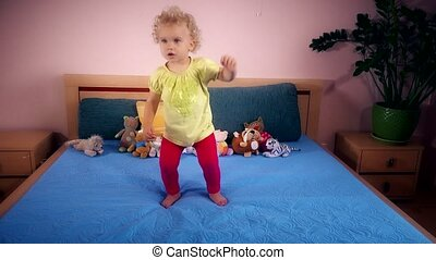Naughty toddler girl jumping and falling on bedroom at home....
