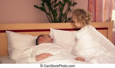 Naughty toddler girl wake up and run away from father bed....