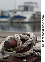 A closeup of a cleat on the dock, with a rope tied around it.