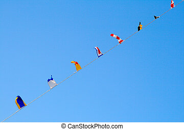Nautical flags against blue sky