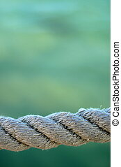 Nautical Image Of Some Weathered Harbor Rope Against A Green Ocean Background With Copy Space