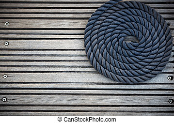 Nautical mooring rope - A curled mooring rope on a wooden ...