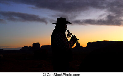 Navajo Native American Indian playing flute at sunrise -...