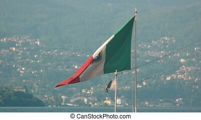 Naval ensign of Italy. Italian flag, Stresa town background....