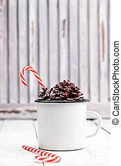navidad, azucare caña, palos, en, estaño blanco, taza, con, abeto, cones., luz, coloreado, photo., espacio, para, text.
