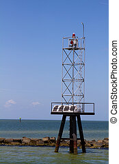 Navigational aid beacon powered by solar energy cells warns shipping away from shallow water and rocky coastlines.