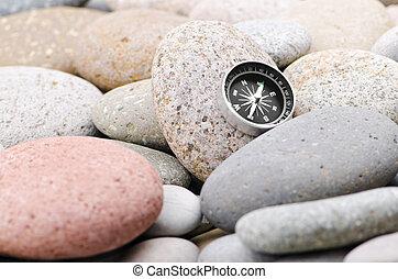 Navigation compass on stone pebbles