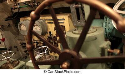 navigator rotates steering wheel depth on board submarine...
