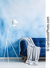 Navy blue couch with gray blanket and white standing lamp against blue and white ombre wall in a living room interior. Real photo.