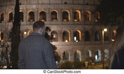 nazad prospekt, od, młody mężczyzna, i, kobieta stanie, blisko, colosseum, w, rzym, włochy, i, tulenie, razem.