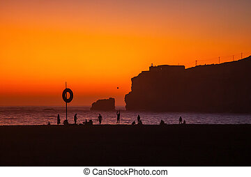 Nazare, Portugal: Amazing orange sunset over Atlantic Ocean and people relaxing on the beach. Lighthouse and Fort of Sao Miguel visible on the high cliff.