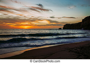 Nazare, Portugal: Sunset over Atlantic Ocean seen from the beach