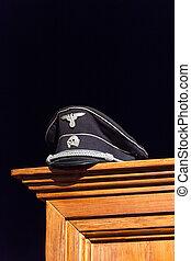 Nazi cap exhibited on wooden wardrobe on black background