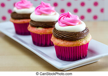 Neapolitan Cupcakes - Line of 3 neapolitan frosted cupcakes...