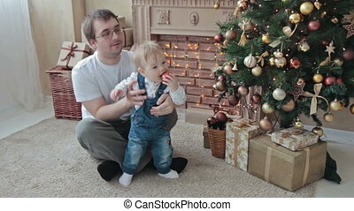Near Christmas tree dad playing with his son