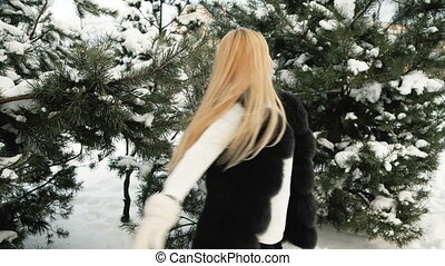 Near snowy trees woman with long white hair to spin on the spot.