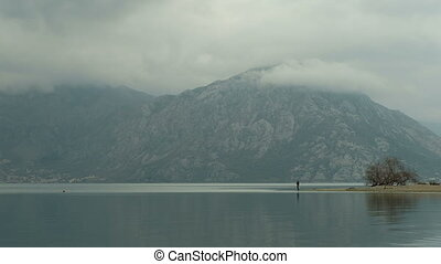 Near the mountains with clouds is a small figure of a fisherman.