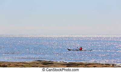 Near the shore of the sea floats a single kayak - Near the...