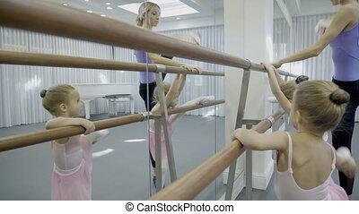 Near wooden ballet machine, learn teacher and young children.