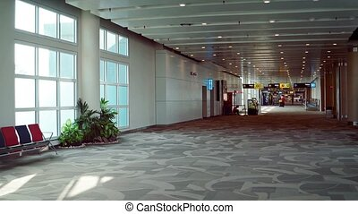 """Nearly empty concourse in an airport terminal with chairs, potted plants and a business stall. Video Full HD"""