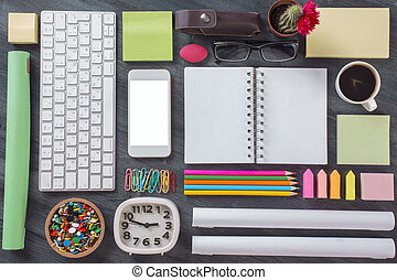 Top view of wooden office desktop with blank white smartphone, keyboard, clock, notepad, coffee cup and other items organized in a neat and creative manner. Mock up