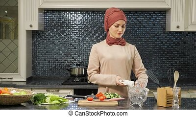 neat housewife in hijab wipes dishes cooking meal for supper...