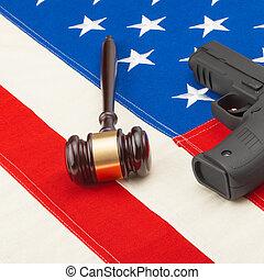 Neat judge gavel and gun over US flag - studio shot