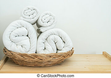 neat rolls of white cotton towel on basket in bedroom for bath