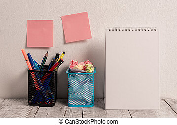 Neat Workplace with 2 Empty Colored Stick Pad Notes Put on White Wall Hanging above 2 Mesh Pencil Pots and Open Spiral Notebook on Work Desk. Working on Project