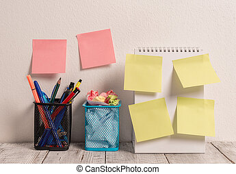 Neat Workplace with 6 Empty Colored Stick Pad Notes Put on Both White Wall and Open Spiral Notebook with 2 Full Pencil Pots on Work Desk. Working on Project