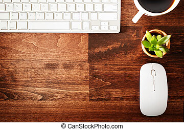 Neat workstation on a wooden desk viewed from overhead with...